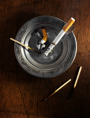 Silver ashtray with cigarette butts and matches on wooden table