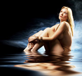 Pale blond beauty naked in studio wearing jewellery poster