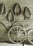 Horse harness and wheels on a wall. poster
