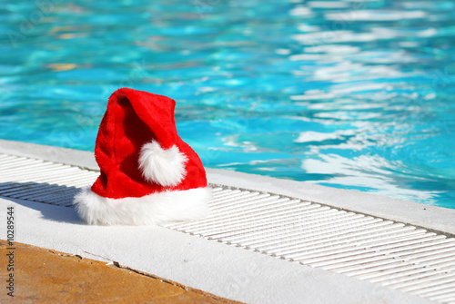 Leinwandbild Motiv Santa hat near the swimming pool