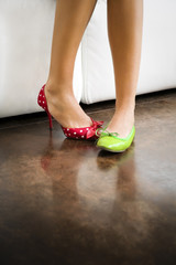 Cropped view of woman wearing mismatched shoes .