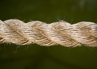 Closeup detail of a rope over a solid green background.