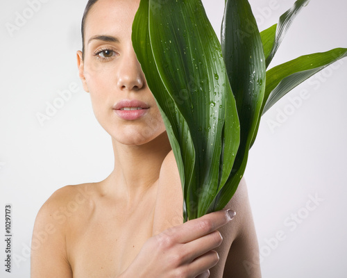 Naked woman holding plant