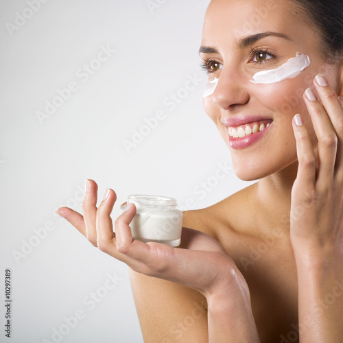 Woman applying lotion.