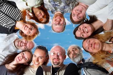 Happy team. 11 peoples. On blue sky.