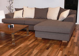 A brownish sofa for three on a hardwood floor poster