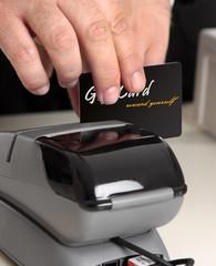 Man swiping a gift card, credit or debit card at pos terminal