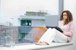 Young creative businesswoman sitting at office window