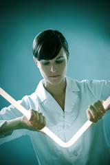 Italian woman holding neon stick in lab