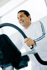 man at the gym doing exercise on a cardio machine