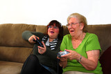 Granddaughter and Grandmother Playing Video Games poster