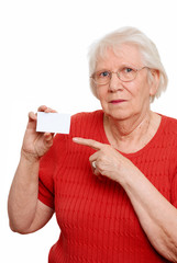 Isolated elderly woman pointing to a business card