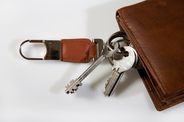 bunch of keys on brown leather wallet