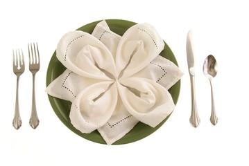 Elegant green table setting Folded linen napkin on a green plate