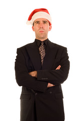 A employee wearing a santa hat, looking grouchy