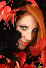 Portrait of the beautiful girl with red hair in a black cape