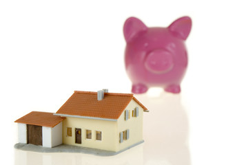 piggy bank and little house isolated on white background
