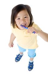 A young asian girl brushing her teeth.