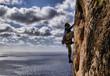 Hombre escalando sobre el mar