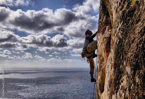 Hombre escalando sobre el mar - 10326920