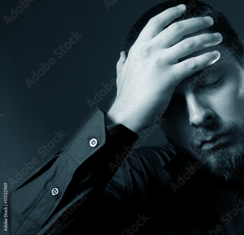 Low key portrait of depressed businessman