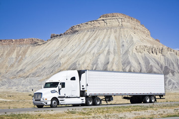 White semi truck driving in Colorado