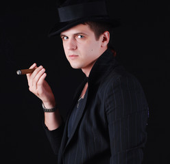portrait of young gangster in black suit with cigar