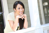 A pretty asian woman at home on the porch