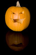 Vertical image of a Jack-o-Lantern on a reflective surface