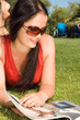 Beautiful young woman reading magazine in the park..