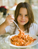young girl eating spaghetti in restaurent