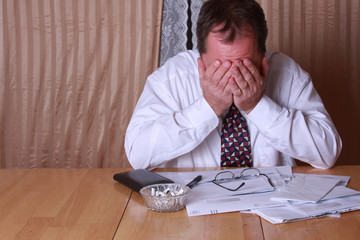 Man stresses out with bills stacking up on the kitchen table.