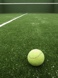 Tennis ball on synthetic grass of paddle court.-