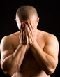muscular man covering his face with the hands