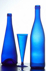 Two dark blue bottles and glass with wate