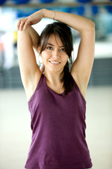 woman at the gym doing arm stretches and smiling