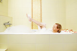 The woman bathes in a bath with foam poster