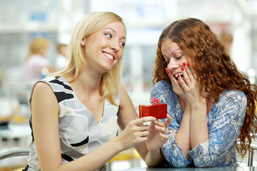 One girlfriend presents a gift another in cafe
