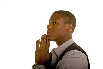 A young black man praying in profile on white