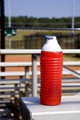 A red watter bottle on the stands of a baseball field