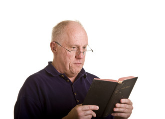 An older bald man in glasses reading the bible with interest