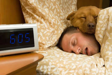 Man and his dog comfortably sleeping in