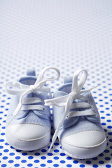 closeup of blue baby shoes on dotted background