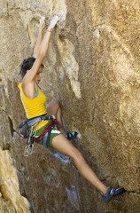 Female climber ascending a steep rock face.