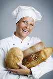 female baker with hands full of bread