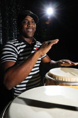 Portrait of young latino percusionist playing african drums