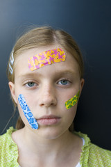 a girl with several colorful bandages on her face, looking sad