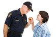 Adolescent boy giving a donut to a friendly police officer.