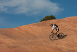 A skilled mountain biker on a red sandstone face. poster