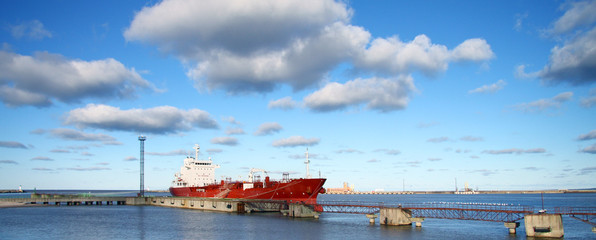 Vessel in sea port under blue sky